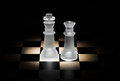 Chess king and queen on a board with black background Stock Photos