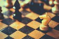 Chess knight and bishop white black figures standing on chessboard toned photo Royalty Free Stock Photo