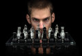 Chess master staring at you with intense eyes behind glass pieces on a glass chessboard with a reflection isolated on a Stock Photo