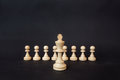 Chess pieces on a black background. The white king stands on the background of pawns Royalty Free Stock Photo