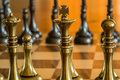 Chess pieces on a chess board macro showing the king queen and bishop and pawn in game the opposing players are in the background Stock Photo