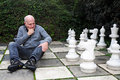 Chess player senior man sitting on a chessboard Royalty Free Stock Photos