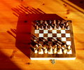 Chess set with shadows a small on a pine disk in bright sunlight casting long Royalty Free Stock Photos