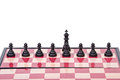 Chessboard with black pawns and king isolated on white background Stock Photography