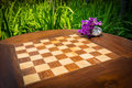 Chessboard in wooden table with flower vase in garden Stock Photo