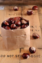 Chestnuts in paper bag craft full of brown on rusted wooden background Stock Photography