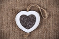 Chia on burlap white wood heart shaped frame filled with seeds brown Stock Photography