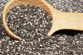 Chia seeds dark and light colored in wooden spoon blurred in foreground and background is an edible seed that comes Royalty Free Stock Photos