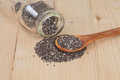Chia seeds spilling out of glass bottle on able Royalty Free Stock Photo