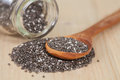 Chia seeds spilling out of glass bottle on table Royalty Free Stock Photo