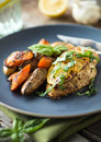Chicken breast with roasted vegetables lemony seasoned fingerling potatoes and carrots Stock Photos