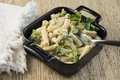 Chicken and broccoli pasta with in an individual baking pan with fork napkin Stock Images