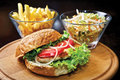 Chicken burger with chicken filet tomatoes green salad onion mayonnaise sauce and french fries Royalty Free Stock Photo