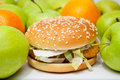 Chicken burger next to many apples and oranges Royalty Free Stock Photo