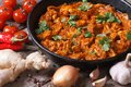 Chicken in curry sauce in a pan with the ingredients on old desk Royalty Free Stock Photos
