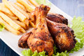 Chicken drumsticks with chips selective focus Royalty Free Stock Photos