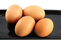 Chicken eggs on black dish four the white background Royalty Free Stock Photography