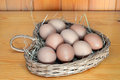 Chicken eggs in a heart shaped wicker basket laid hay Royalty Free Stock Photography