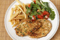 Chicken escalopes meal high angle breaded schnitzels or with french fries and a tomato and green salad Royalty Free Stock Photography