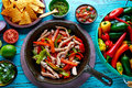 Chicken fajitas in a pan chili and sides mexican with sauces food Royalty Free Stock Images