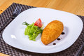 Chicken kiev with leaf salad and tomato on white plate Royalty Free Stock Photo