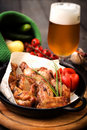 Chicken legs with beer and vegetables on a plate green Stock Images