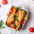 Chicken legs fried with mushrooms and tomatoes. Royalty Free Stock Photo