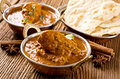 Chicken madras with naad bread as closeup on a wooden table Stock Image