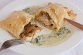 Chicken with mushrooms in puff pastry with cream sauce basil and spinach on white plate Stock Photos