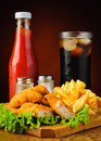 Chicken nuggets french fries cola and ketchup still life with menu tomato Royalty Free Stock Images
