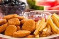 Chicken nuggets and french fries with watermelon blueberries in the background Royalty Free Stock Photos