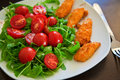 Chicken nuggets with salad close up baked ruccola and tomatoes Stock Photography