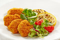 Chicken nuggets and vegetables on a white plate Royalty Free Stock Image