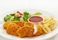 Chicken nuggets and vegetables on a white plate Royalty Free Stock Images