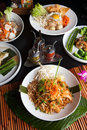 Chicken pad thai with a variety of other fine food dishes shallow depth of field Stock Photos