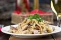 Chicken pasta meal on table rustic wooden with a glass of drink napkins and condiments Stock Photos