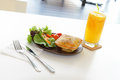 Chicken pie with salad and orange juice a meal of a glass of cold on table in a cafe Royalty Free Stock Images