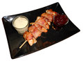 Chicken rolled up with bacon and sauces isolated on white a plate mustard sauce barbecue sauce a black plate background Royalty Free Stock Photography