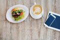 Delicious breakfast on the table. Chicken sandwich, Cup of coffee and smartphone on the table Royalty Free Stock Photo