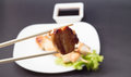 Chicken shashlik isolated on black background put on a white dish decorated with salad and soy sauce Stock Photography