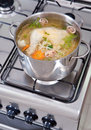 Chicken soup being cooked on a gas stove Stock Images