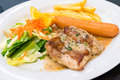 Chicken steak with sausage and salade  on white dish Royalty Free Stock Photo