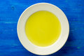 Chicken stock bouillon broth clear soup in a white plate on a blue board top view Stock Photos