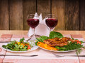 Chicken with vegetables and salad with two glasses of red wine grilled on table in wooden restaurant interior Stock Photo