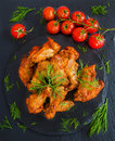 Chicken wings cooked with barbecue sauce on black stone background. Small cherry tomatoes and dill. Top view Royalty Free Stock Photo