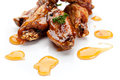 Chicken wings fried in honey sauce on a white background Stock Images