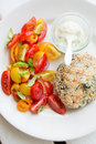 Chickenburger with tomato salad sesame seeds and Stock Photo