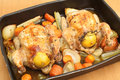 Chickens roasted on vegetables a bed of carrot onion garlic and celery and stuffed with a lemon and some herbs using a bed of Royalty Free Stock Image