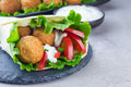 Chickpea falafel balls with vegetables and sauce, roll sandwich preparation Royalty Free Stock Photo