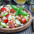 Chickpea salad with cherry tomatoes, cucumbers, basil and onion with citrus dressing, square format Royalty Free Stock Photo